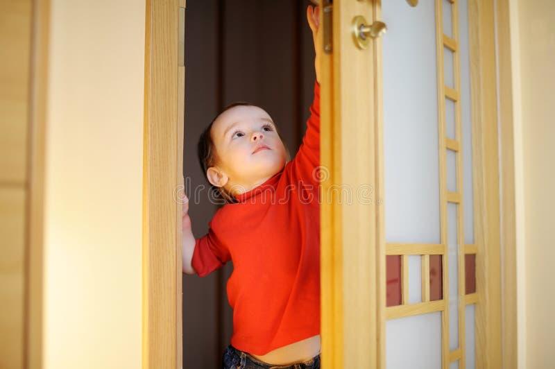 Bambina che prova ad aprire un portello fotografie stock libere da diritti