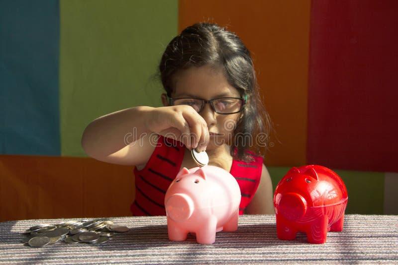 Bambina che prova a mettere le monete nel suo porcellino salvadanaio, Pune, India immagine stock