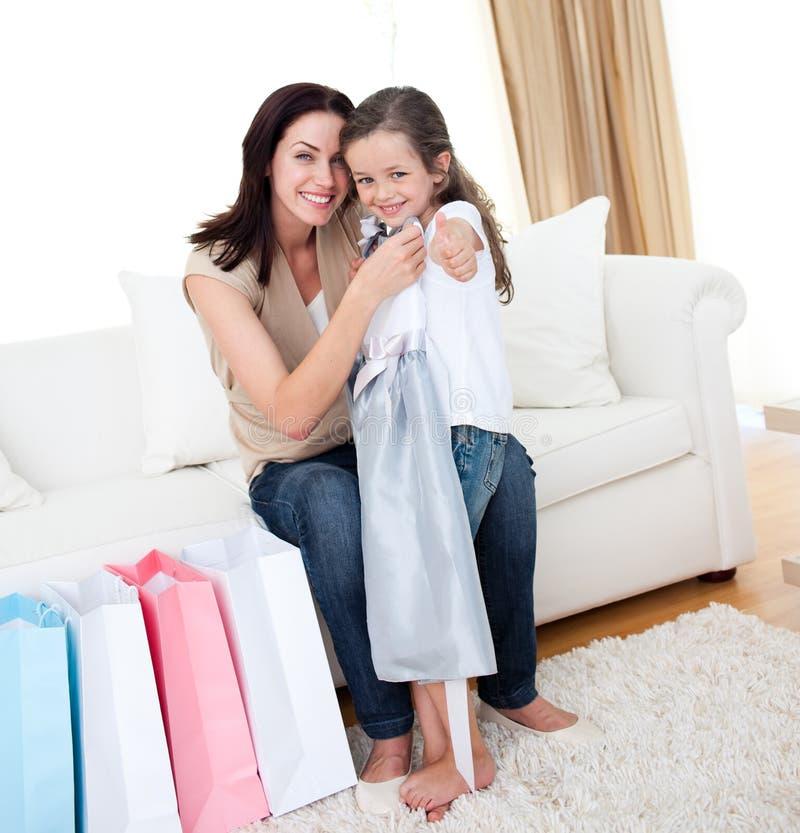 Bambina che prova su un vestito con la sua madre fotografie stock libere da diritti