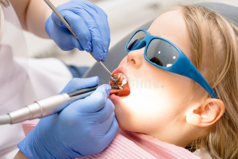 Bambina che riceve procedura di riempimento dentaria in clinica dentaria pediatrica fotografia stock