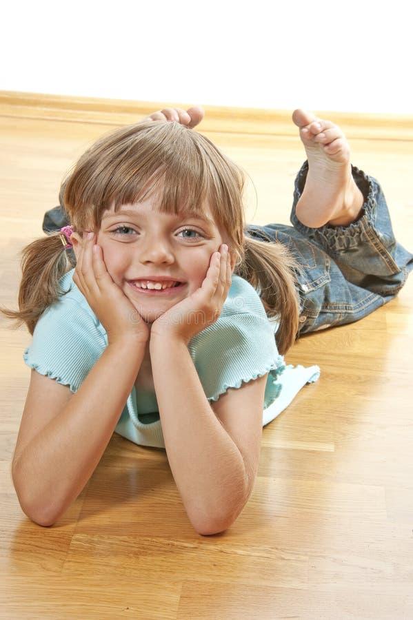 Bambina che riposa su un pavimento di legno immagini stock