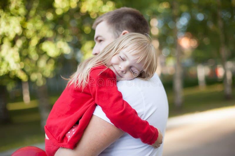Bambina che riposa sulla spalla di suo padre immagini stock