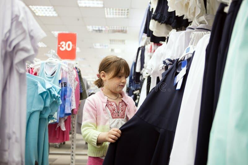Bambina che sceglie i vestiti per la scuola in deposito fotografia stock libera da diritti