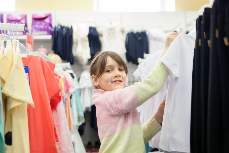 Bambina che sceglie i vestiti prima della scuola in deposito fotografia stock libera da diritti