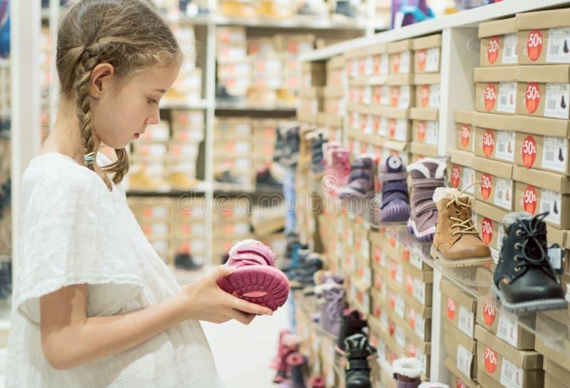 Bambina che sceglie le scarpe di inverno fotografia stock