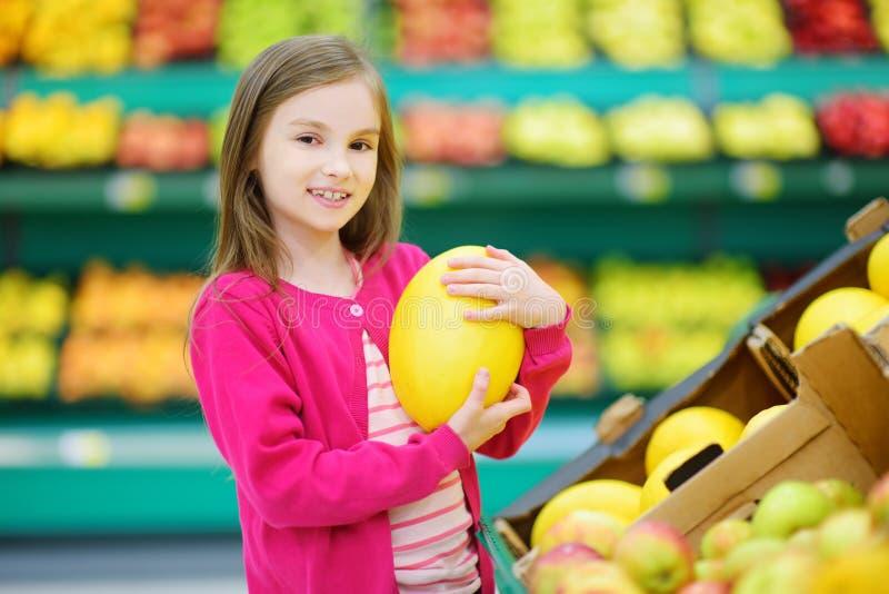 Bambina che sceglie un melone negli alimentari o in un supermercato immagini stock