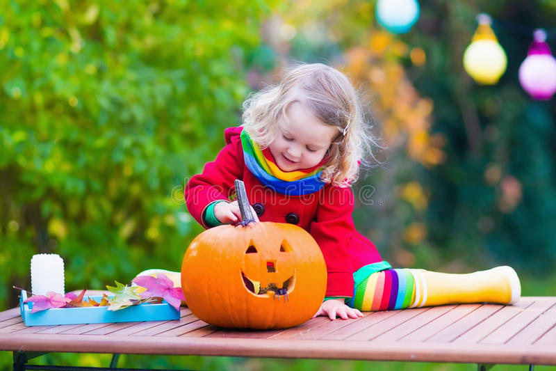 Bambina che scolpisce zucca a Halloween immagine stock libera da diritti