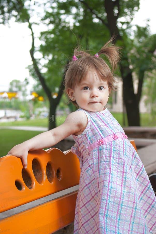 Bambina che si leva in piedi sul banco in sosta fotografia stock libera da diritti