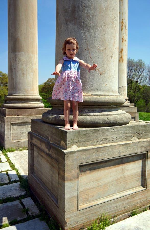 Bambina che si leva in piedi sulla colonna fotografia stock