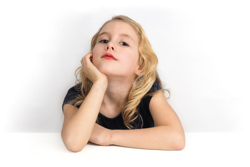 Bambina che si siede ad una tavola e che guarda a me con curiosità immagine stock