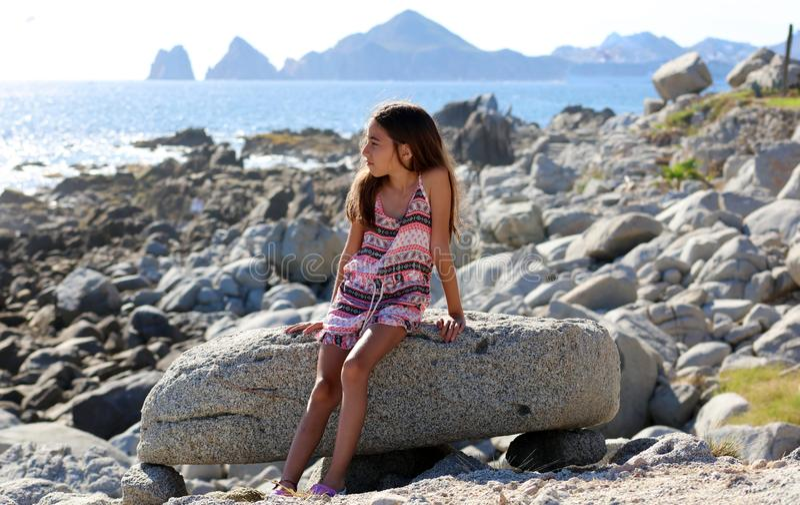 Bambina che si siede alle rocce alla parte anteriore di oceano nel mare della scogliera della località di soggiorno di Los Cabos  fotografia stock libera da diritti