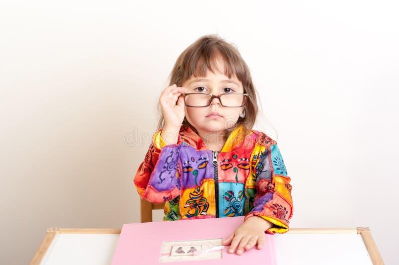 Bambina che si siede allo scrittorio e che esamina i suoi vetri fotografia stock