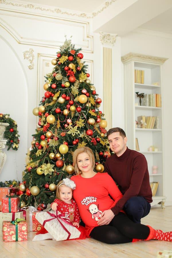 Bambina che si siede con il padre e la madre incinta vicino all'albero di Natale e che tiene i regali immagini stock libere da diritti