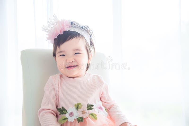 Bambina che si siede davanti alla finestra luminosa fotografia stock libera da diritti