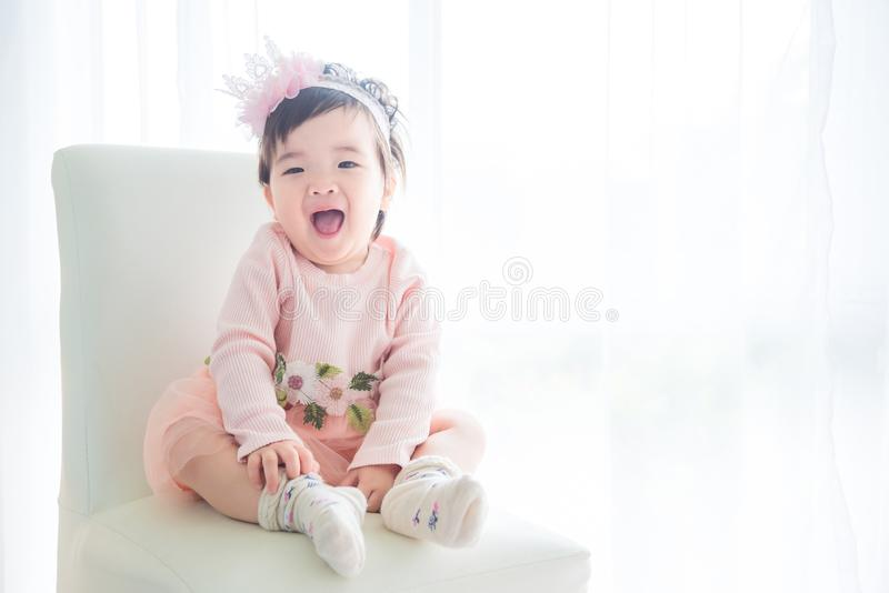 Bambina che si siede davanti alla finestra luminosa fotografie stock