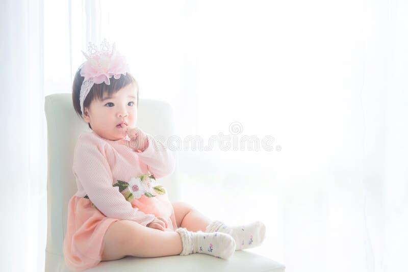 Bambina che si siede davanti alla finestra luminosa fotografie stock libere da diritti