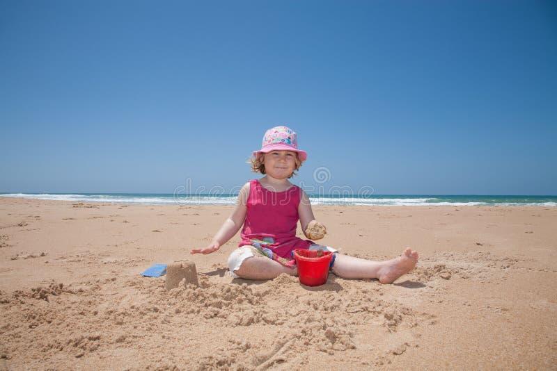 Bambina che si siede facendo un castello in spiaggia di sabbia immagine stock
