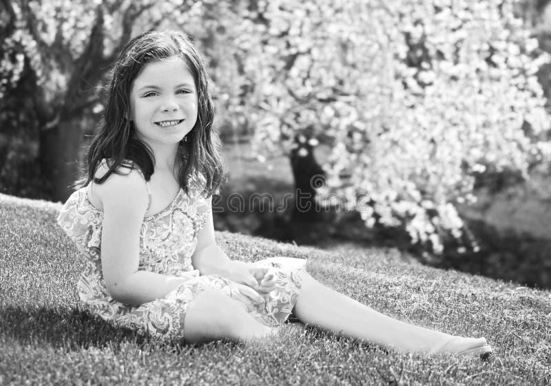 Bambina che si siede nell'erba fotografia stock libera da diritti