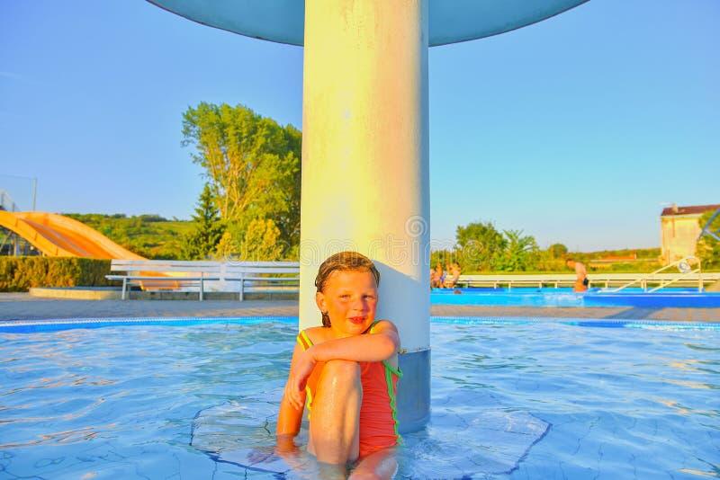 Bambina che si siede sotto uno spruzzatore, doccia nella piscina Ritratto di piccola ragazza sveglia nella piscina Estate soleggi fotografia stock libera da diritti