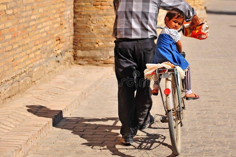 Bambina che si siede su una bici di suo nonno fotografia stock libera da diritti