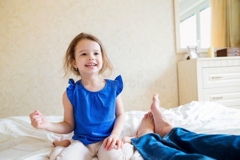 Bambina che si siede sul letto accanto a suo padre fotografia stock immagine di padre - Letto che si chiude ...