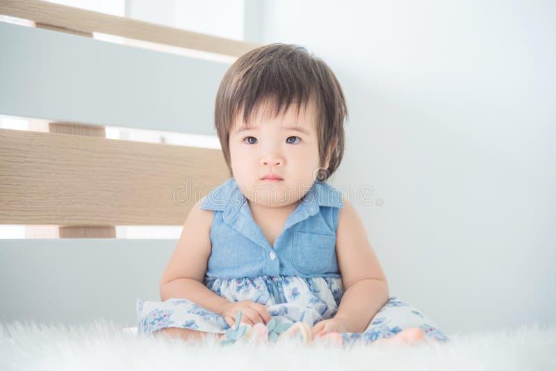 Bambina che si siede sul letto in camera da letto immagine stock