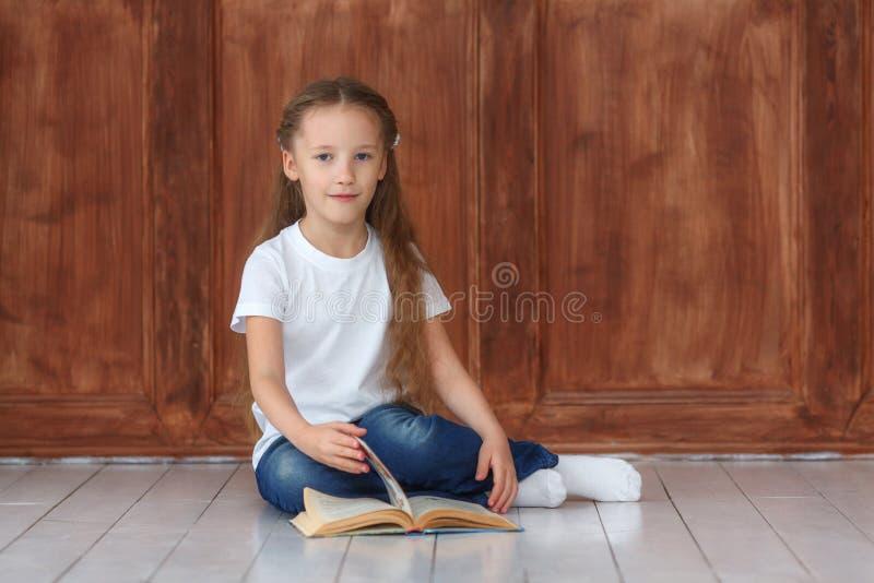Bambina che si siede sul libro di legno di lettura e del pavimento immagine stock