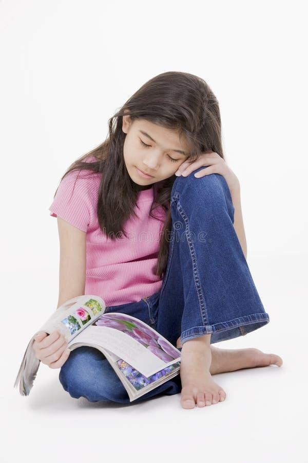 Bambina che si siede sul pavimento che legge uno scomparto fotografia stock libera da diritti