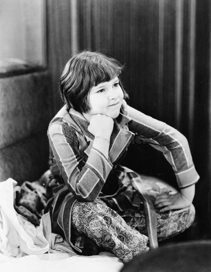 Bambina che si siede sul pavimento con la mano sul mento (tutte le persone rappresentate non sono vivente più lungo e nessuna pro immagini stock libere da diritti