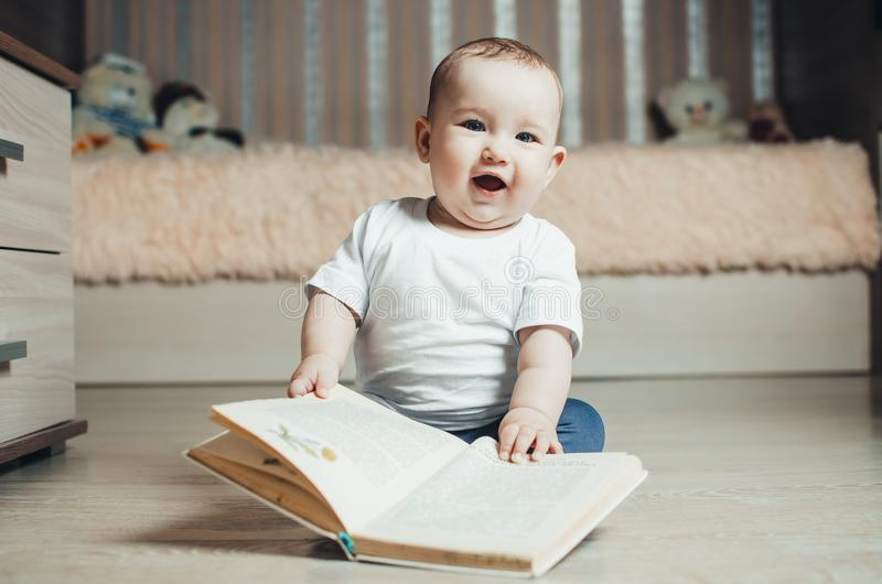 Bambina che si siede sul pavimento con un libro fotografia stock
