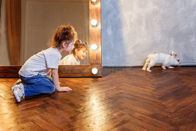 Bambina che si siede sul pavimento e che gioca con il coniglietto bianco del coniglio nella stanza moderna sopra lo specchio fotografie stock libere da diritti