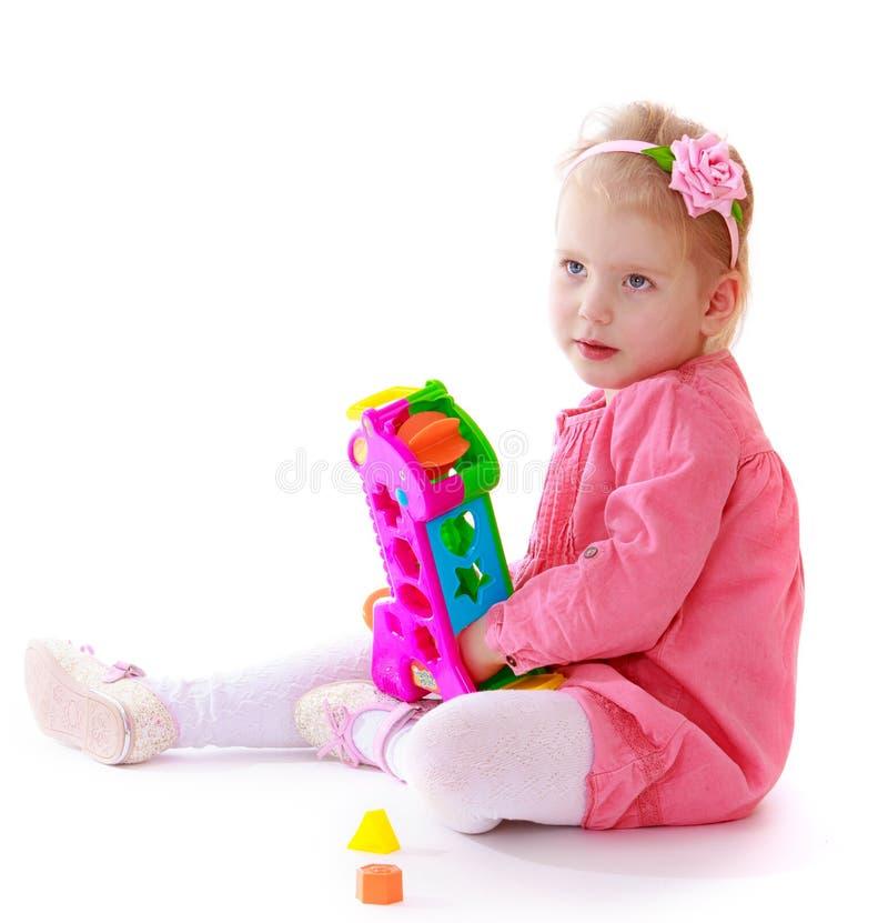Bambina che si siede sul pavimento e sui giochi con fotografia stock