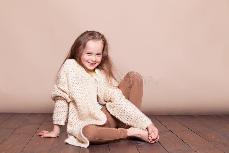 Bambina che si siede sul pavimento e sui sorrisi fotografia stock libera da diritti