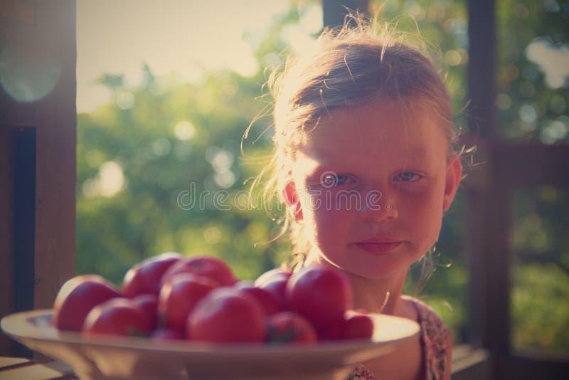 Bambina che si siede sul portico di estate Pomodori sul piatto Immagine vaga e romantica Estate e concetto felice di infanzia immagine stock libera da diritti