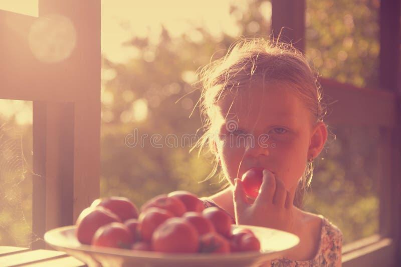 Bambina che si siede sul portico di estate Pomodori sul piatto Immagine vaga e romantica Estate e concetto felice di infanzia immagini stock