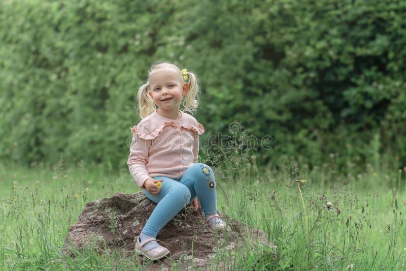 Bambina che si siede sulla pietra immagine stock libera da diritti