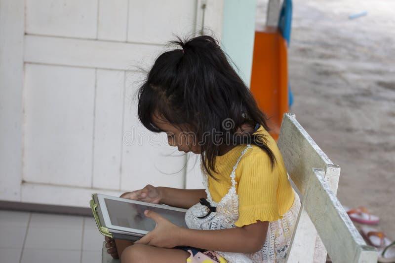 Bambina che si siede sulla sedia e che gioca compressa fotografie stock