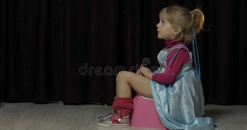 Bambina che si siede sulla TV banale e di sorveglianza fotografia stock