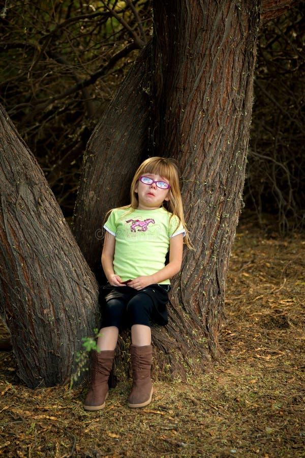 Bambina che si siede in un gridare dell'albero immagini stock libere da diritti