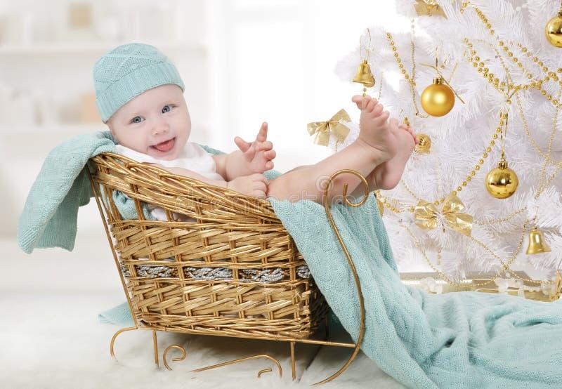 Bambina che si siede in una slitta sotto un albero di Natale fotografie stock libere da diritti