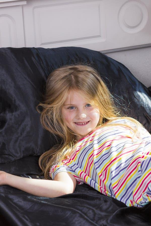 Bambina che si trova a letto a casa fotografia stock libera da diritti