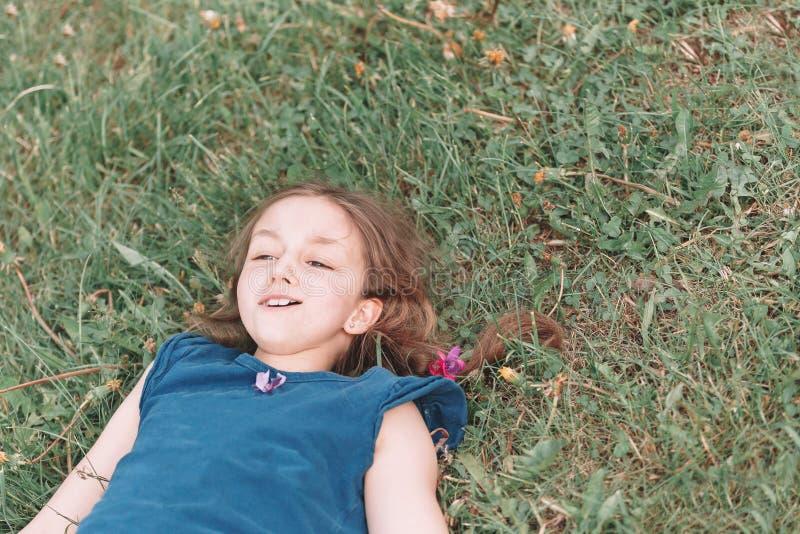Bambina che si trova sull'erba verde un giorno di estate caldo fotografia stock