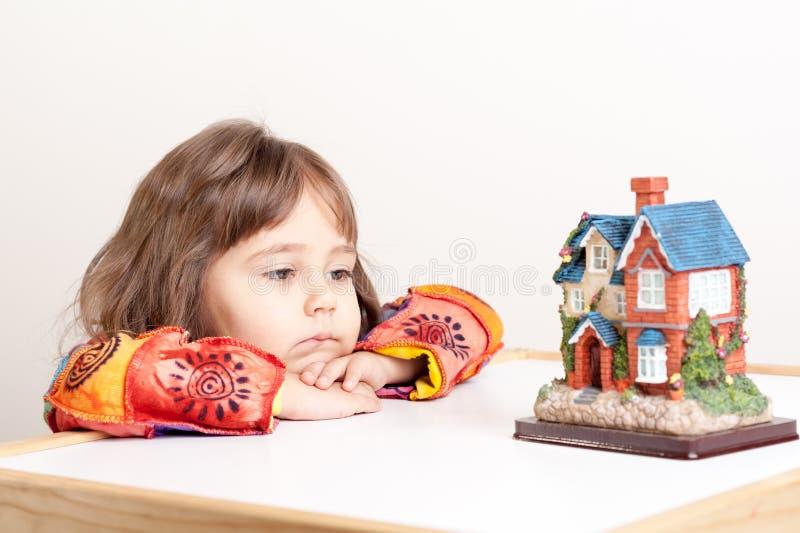 Bambina che sogna della casa immagine stock