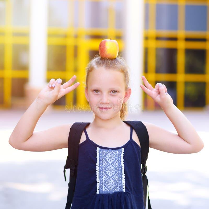 Bambina che sorride con Apple sulla sua testa immagine stock