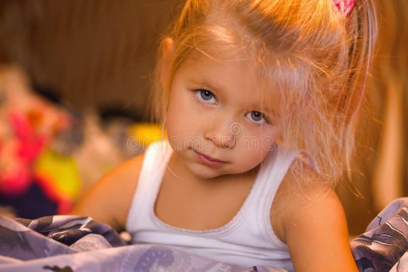 Bambina che sorride e che gioca a letto, sera immagine stock