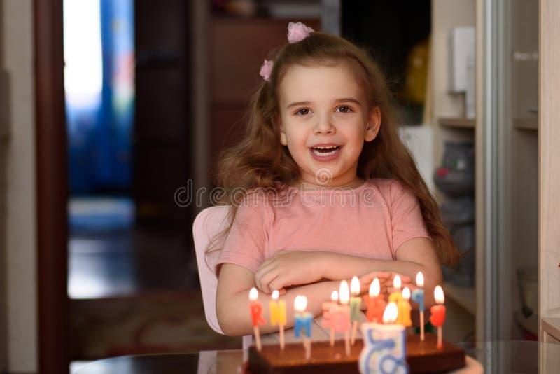 Bambina che spegne le candele su una torta di compleanno sul suo spazio della copia di compleanno fotografie stock libere da diritti