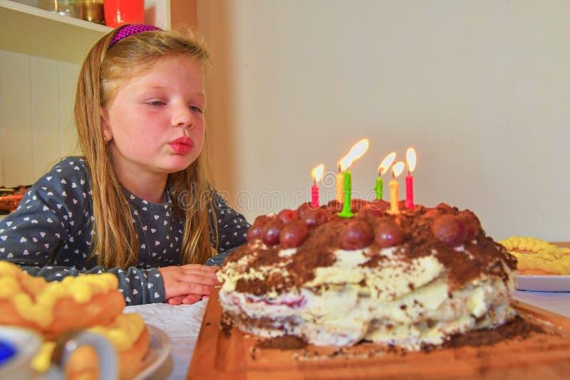 Bambina che spegne le candele sulla sua torta di compleanno Piccola ragazza che celebra i suo sei compleanni Torta di compleanno  fotografie stock libere da diritti