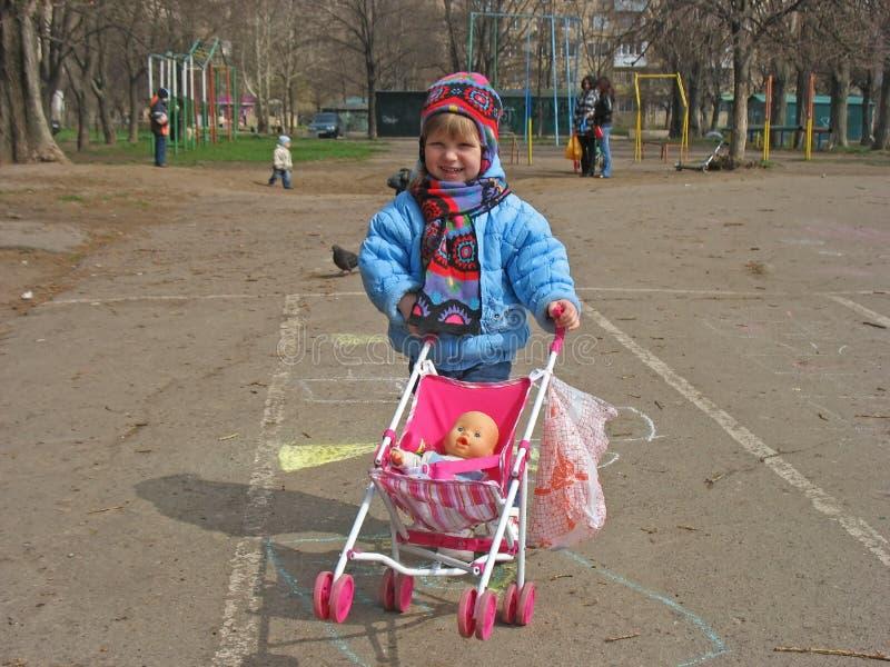 Bambina che spinge un carrello in una carrozzina immagine stock libera da diritti