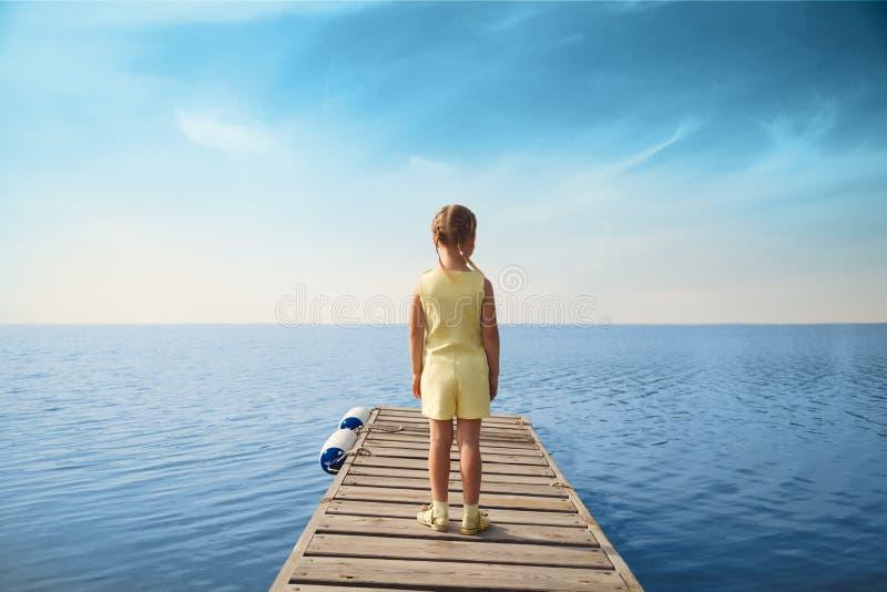 Bambina che sta al pilastro di legno e che guarda al mare immagini stock