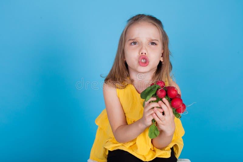 Bambina che tiene le verdure sane di un alimento dei ravanelli rossi fotografie stock libere da diritti